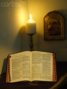 Open Bible with a Lit Candle Behind